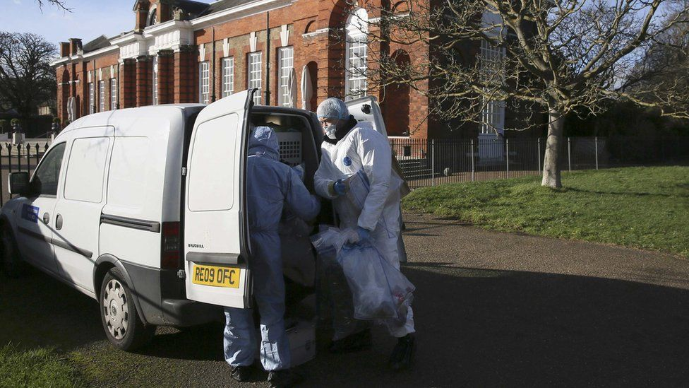 Forensic police officers put evidence into a van in an area near the grounds of Kensington Palace