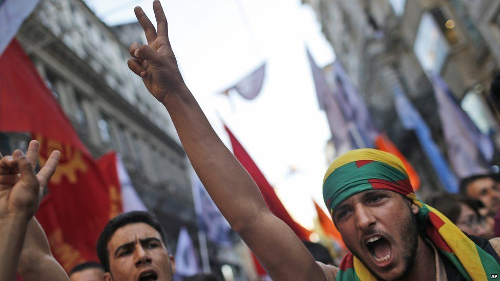 Protesters flash the V-sign as they chant slogans during a protest in Istanbul, Monday, July 20, 2015