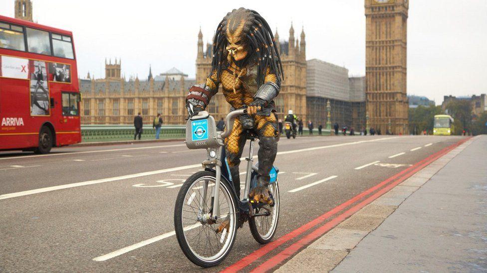 Person dressed as Predator on bike