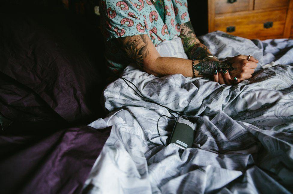 Melanie Semple in bed using a TENS machine