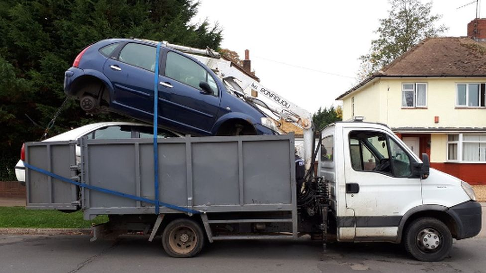 Van with cars strapped to trailer