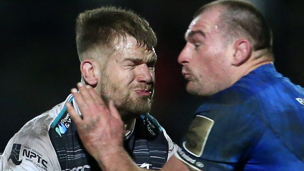 Dan Baker of Ospreys is tackled by Rhys Ruddock