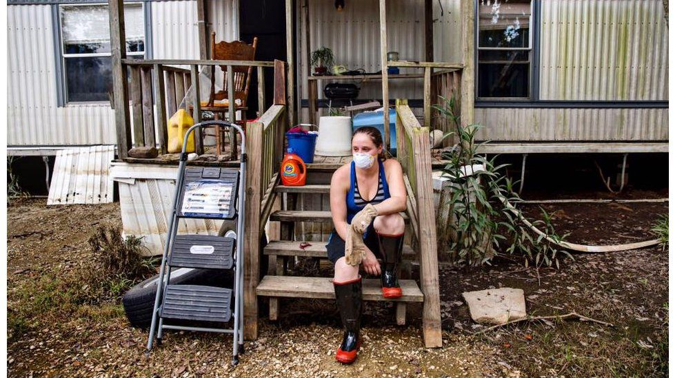 """Stephanie M, 29, takes a break from cleaning her parents' home in St Amant. One of the items they saved is her great-grandmother's table, which had already been restored several times and will now need more repairs. """"I have three family members living with us. They don't know what they're going to do,"""" she said. """"My mom is not coming back here. It's just too much. They are going to stay as long as they need to."""""""