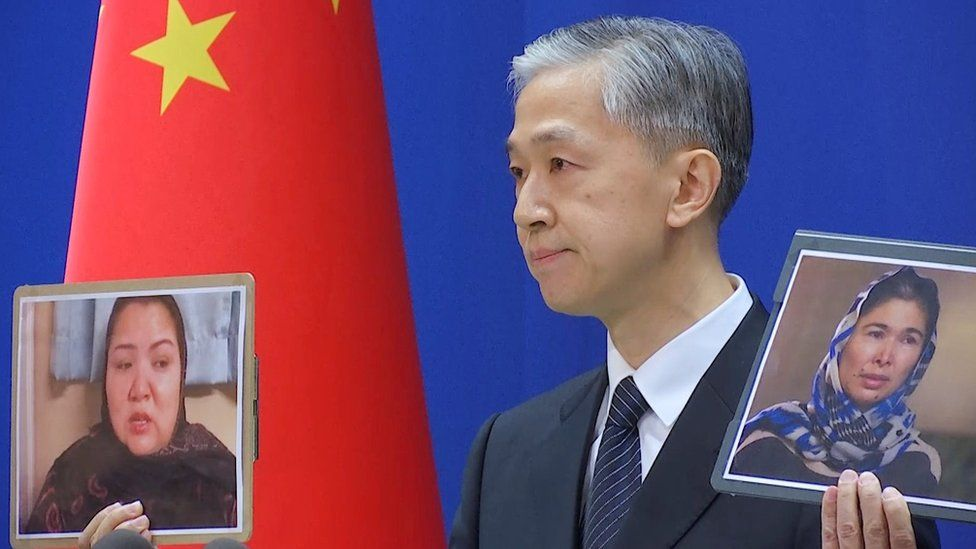 Chinese Foreign Ministry spokesman Wang Wenbin holds pictures while speaking during a news conference in Beijing, China February 23, 2021,