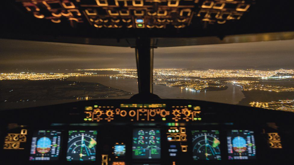 The lights of a city seen from the cockpit of the plane that flies Santiago Borja