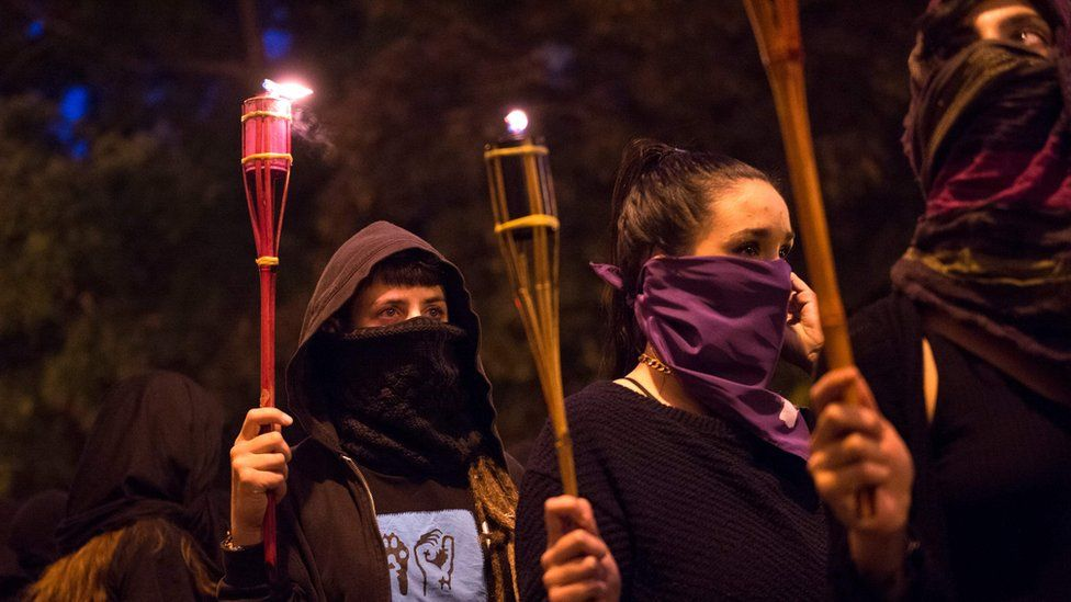 Women covering their faces with black scarves demonstrate, carrying torches