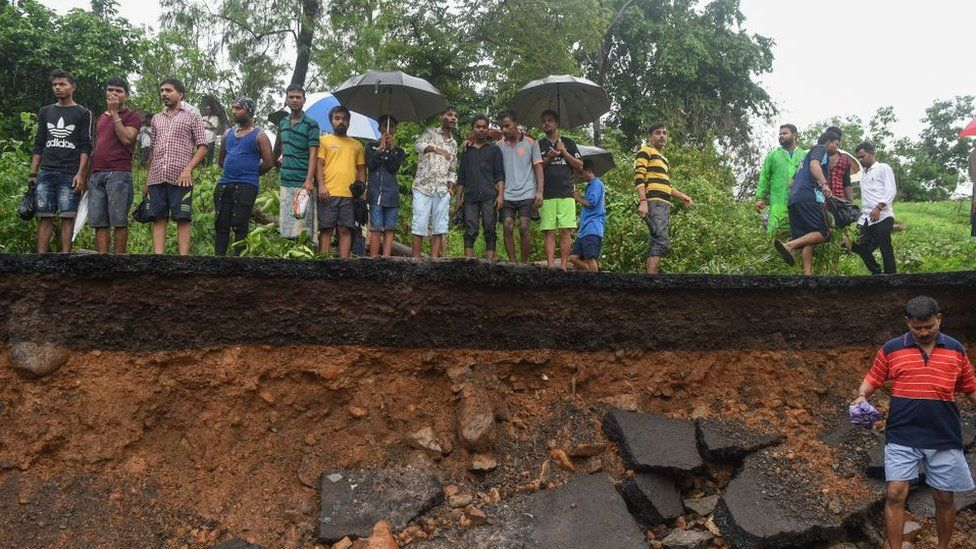 Onlookers gather at the site of a wall collapse in Mumbai on July 2, 2019