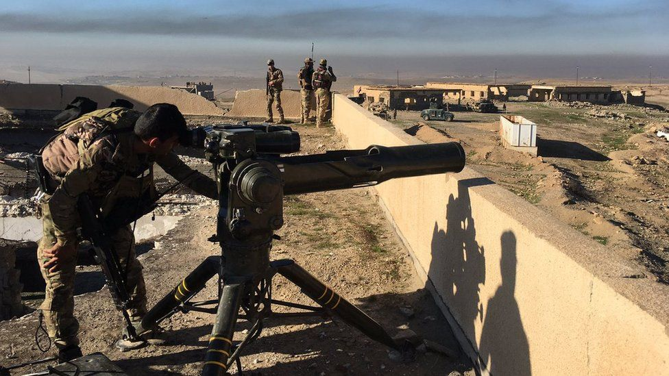 A soldier looks through the site of a mortar, set up on a rooftop