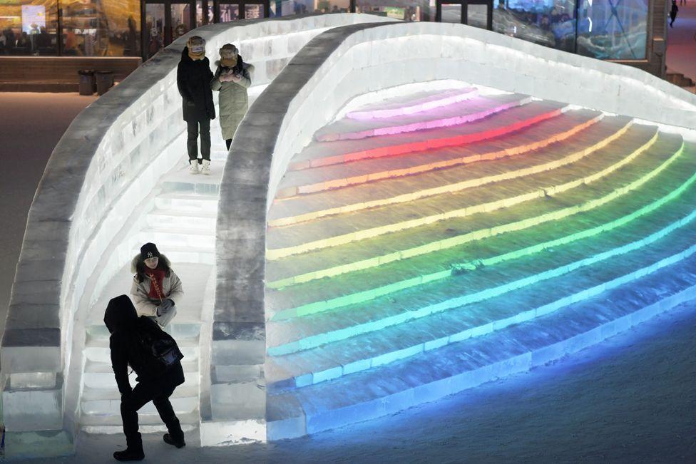 People walk on an ice bridge lit up in rainbow colours
