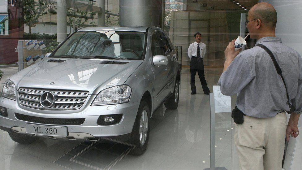 Man looking through window at new car