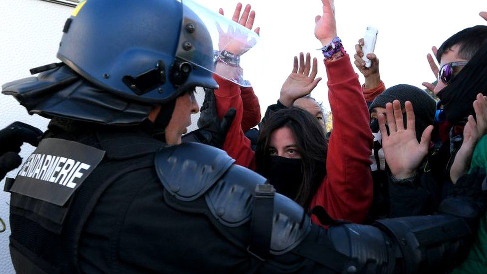 Protesters confront a French gendarme at the AP-7 highway at the Spanish-French border in La Jonquera northern Spain, 11 November 2019