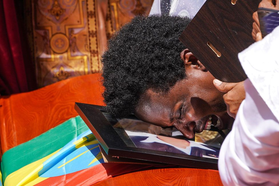 A mourner cries on the coffin of his loved one during a memorial service for the Ethiopian passengers and crew who perished in the Ethiopian Airways ET302 crash