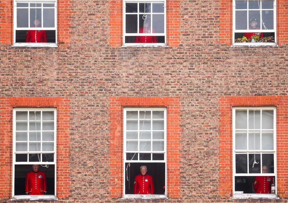 Chelsea pensioners watch a Remembrance Sunday service from their windows at the Royal Hospital Chelsea