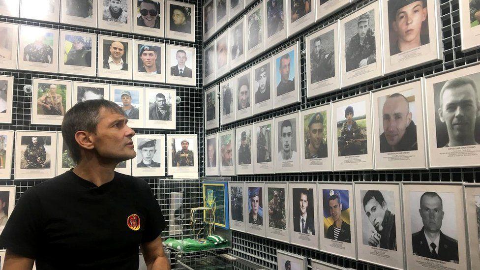 Survivor Roman Zinenko looks at a wall of victims of the battle of Ilovaisk