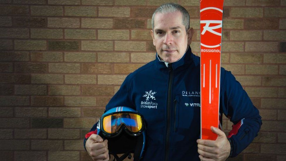 Chris Lloy holding skis