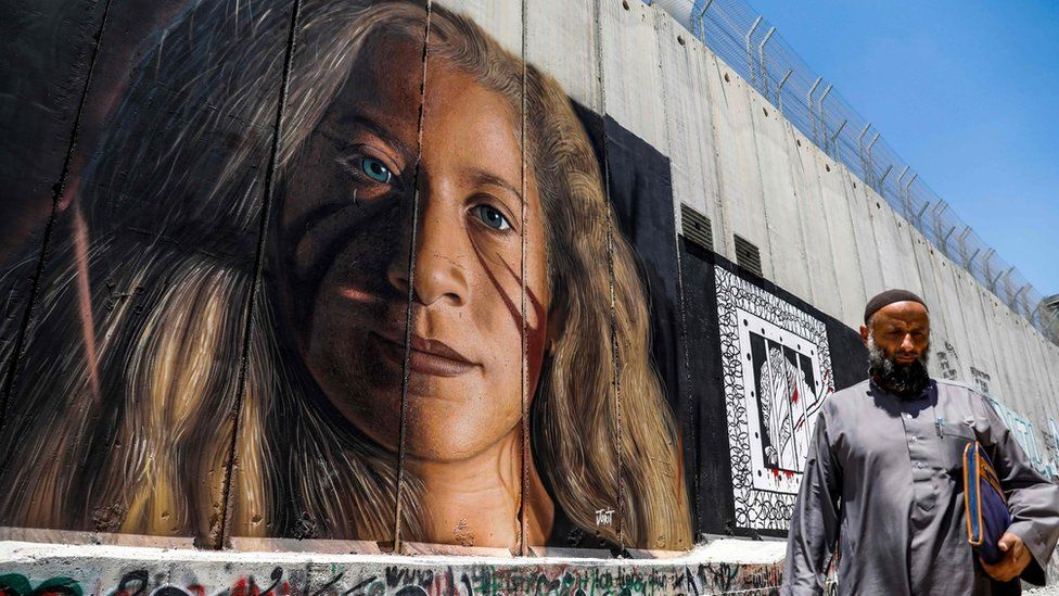 A Palestinian walks past a mural painted on Israel's controversial separation barrier in the West Bank city of Bethlehem on July 29, 2018