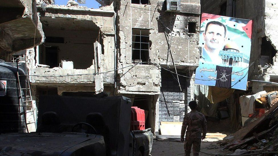 A man walks under a portrait of Syrian President Bashar al-Assad in a street inside the Yarmuk Palestinian refugee camp in the Syrian capital Damascus