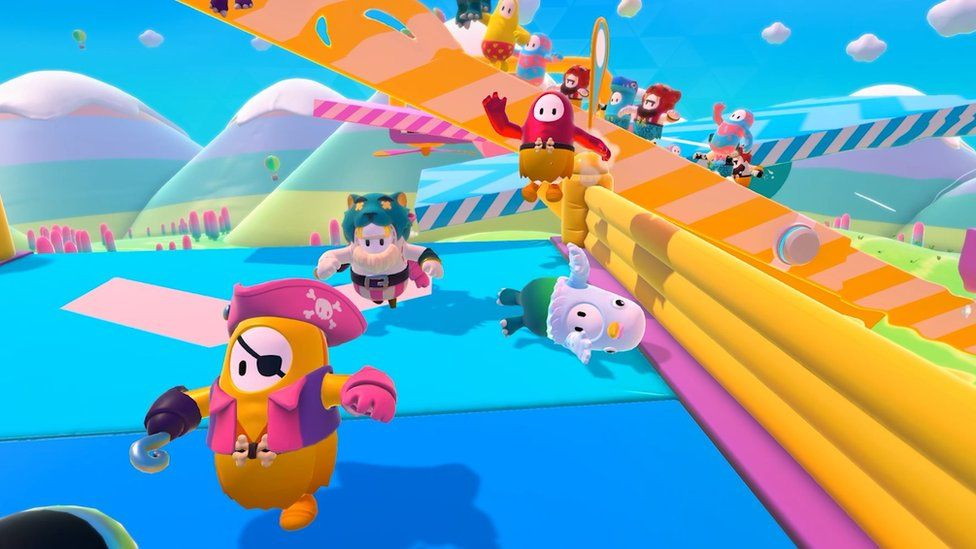 Jellybean-like figures with arms and legs leap through an obstacle course wearing a variety of silly costumes