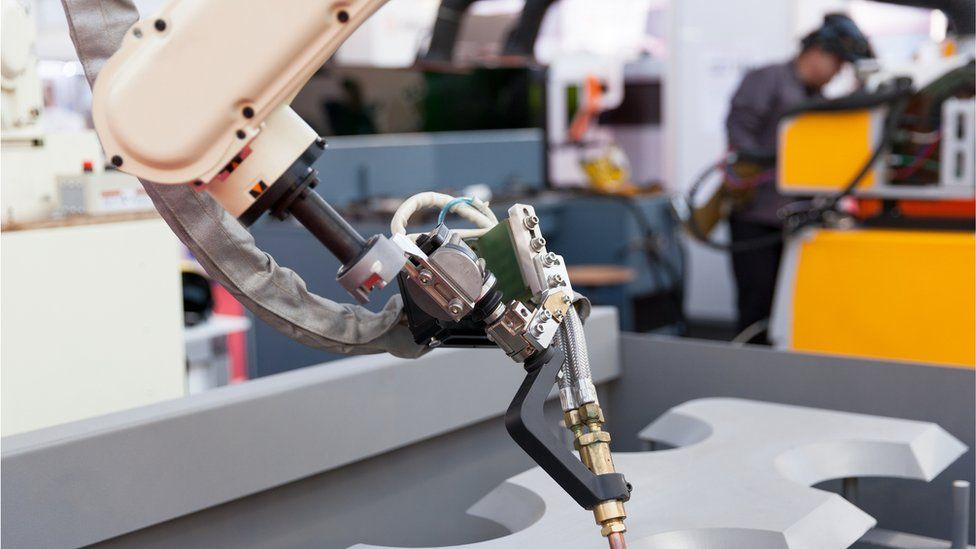A robot arm works on a car, alongside a factory worker
