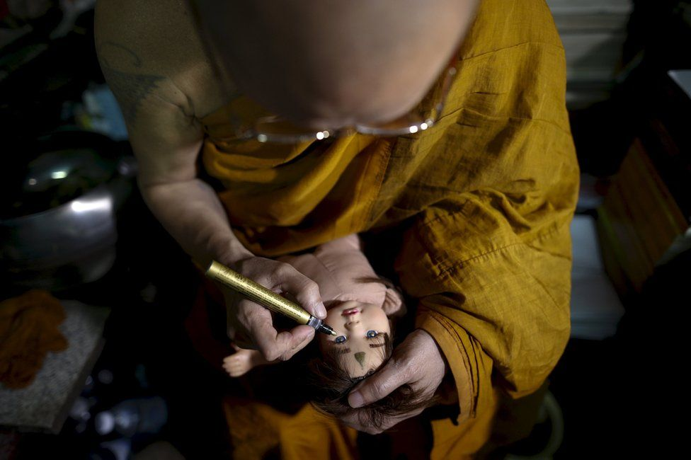 """Buddhist monk Phra Winai Thidtapanyo, 64, anoints on a """"child angel"""" doll during a blessing ritual at Wat Bua Khwan temple in Nonthaburi, Thailand, 26 January 2016."""
