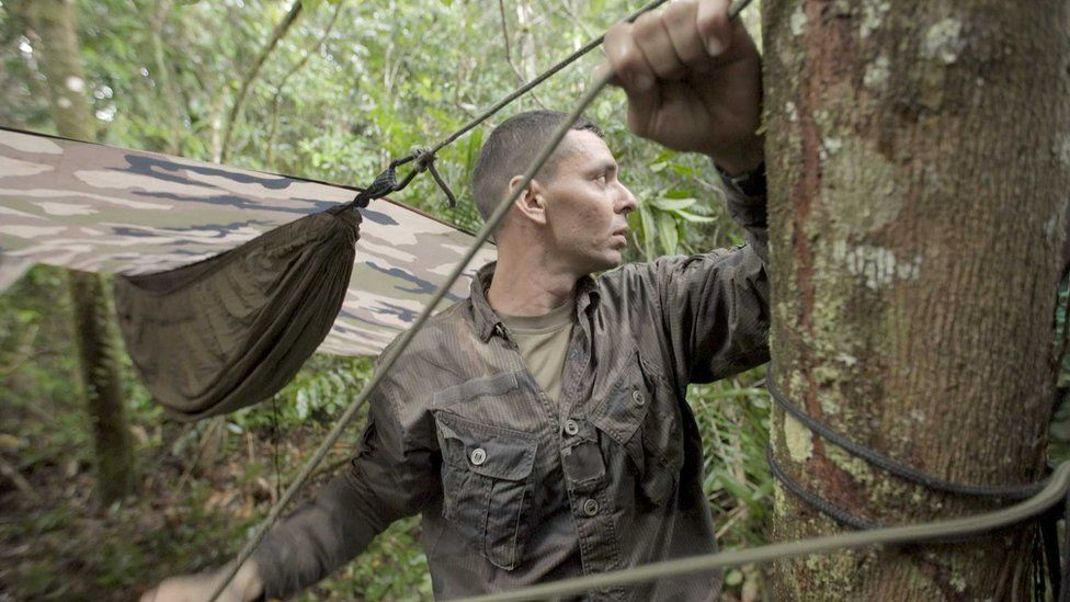 A legionnaire erects his hammock in the forest