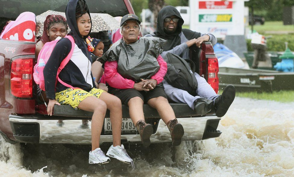 At least five people in the back of a pick up truck as it drives through water
