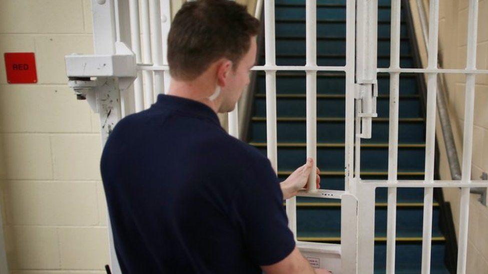 A prison officer locking a gate