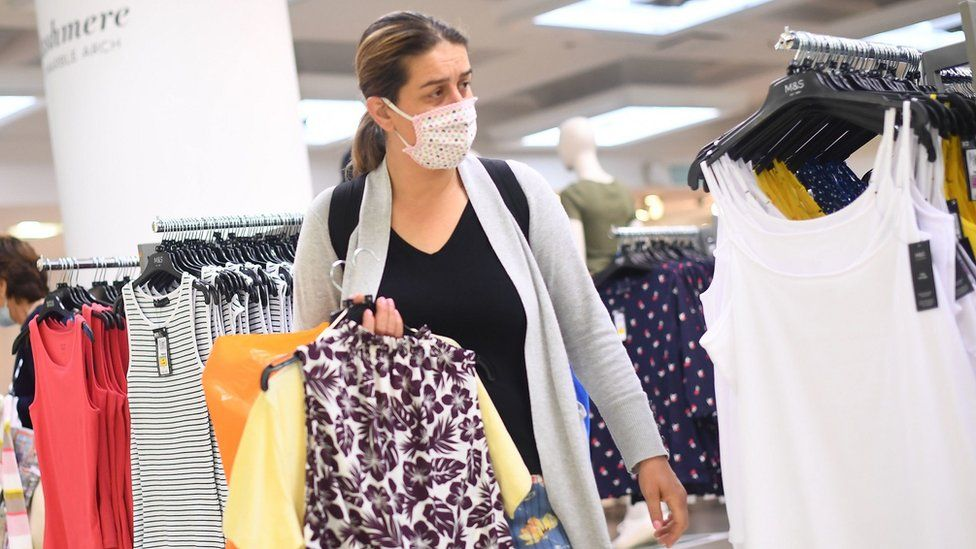 Woman wearing a face covering in a shop