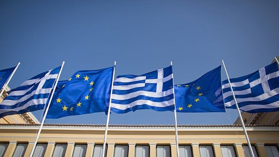 The national flag of Greece and the flag of the European Union fly above a government building.
