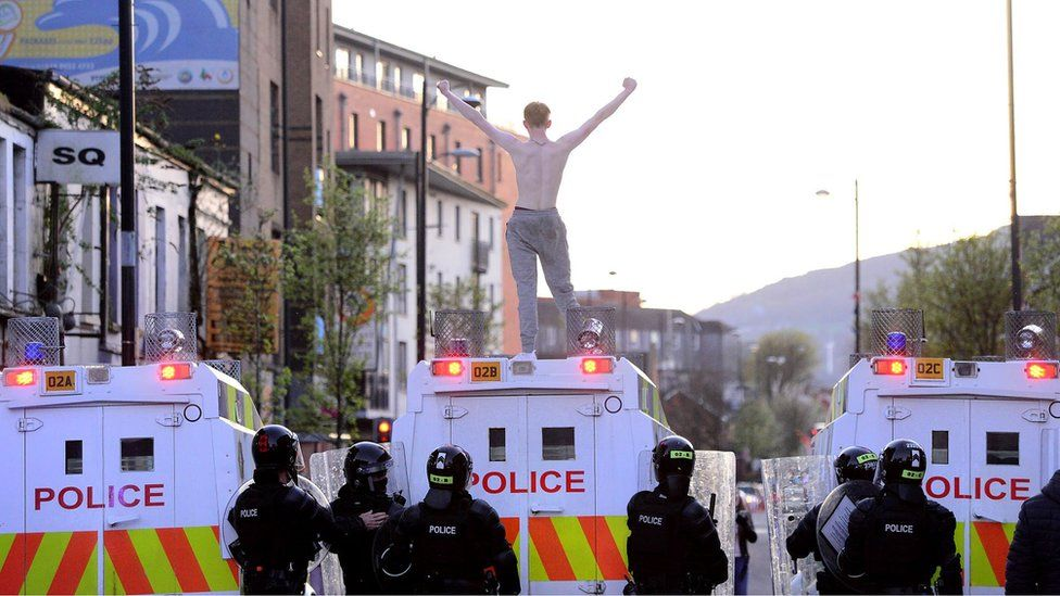 Man stands on top of police land rover in Belfast on 2 April