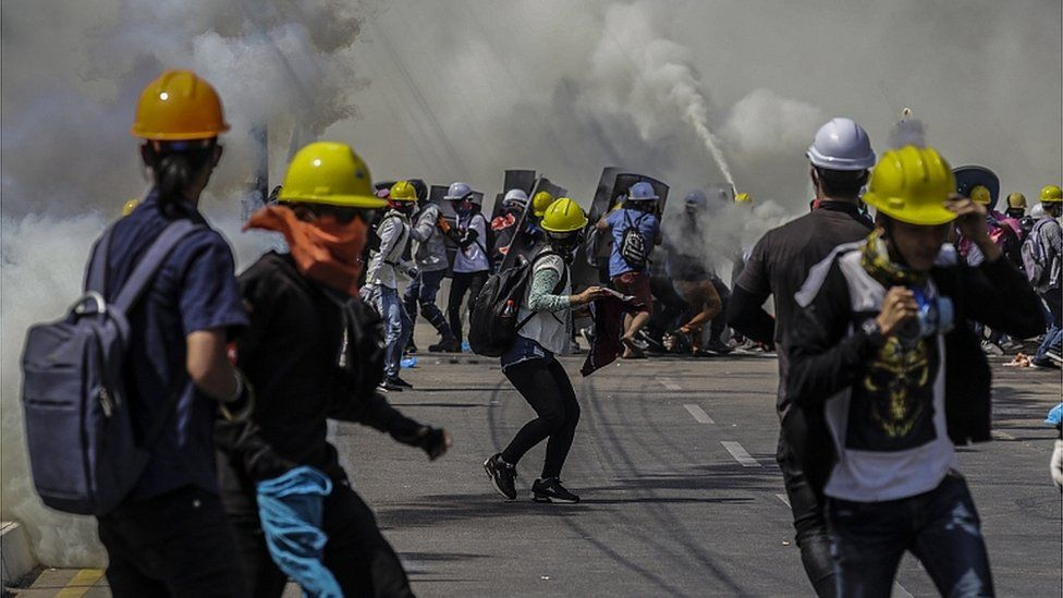 Demonstrators react as tear gas is fired by police during a protest against the military coup in Yangon, Myanmar, 06 March 2021