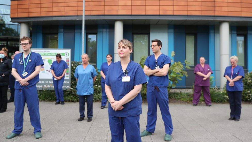 "Staff stand outside Salford Royal Hospital in Manchester during a minute""s silence to pay tribute to the NHS staff and key workers who have died during the coronavirus outbreak."