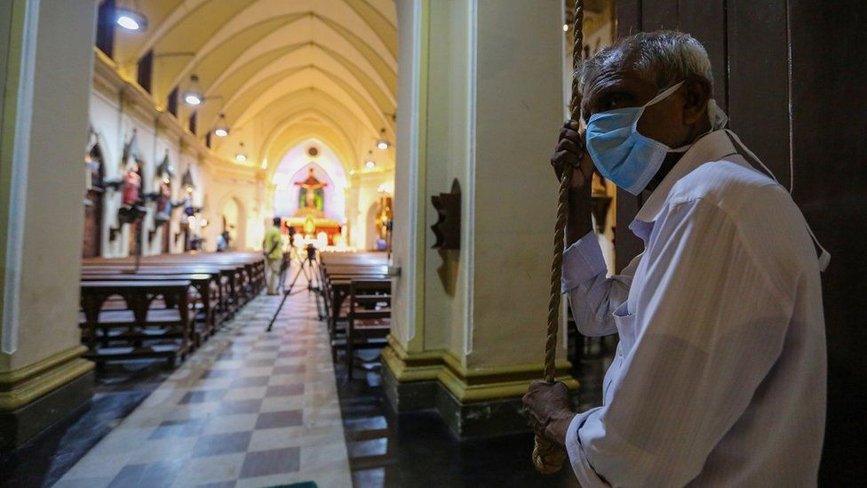 A Sri Lankan man wearing a protective mask ring the church bells for the start of Easter Sunday service at the almost deserted all Saints church during an island-wide curfew, in Colombo, Sri Lanka