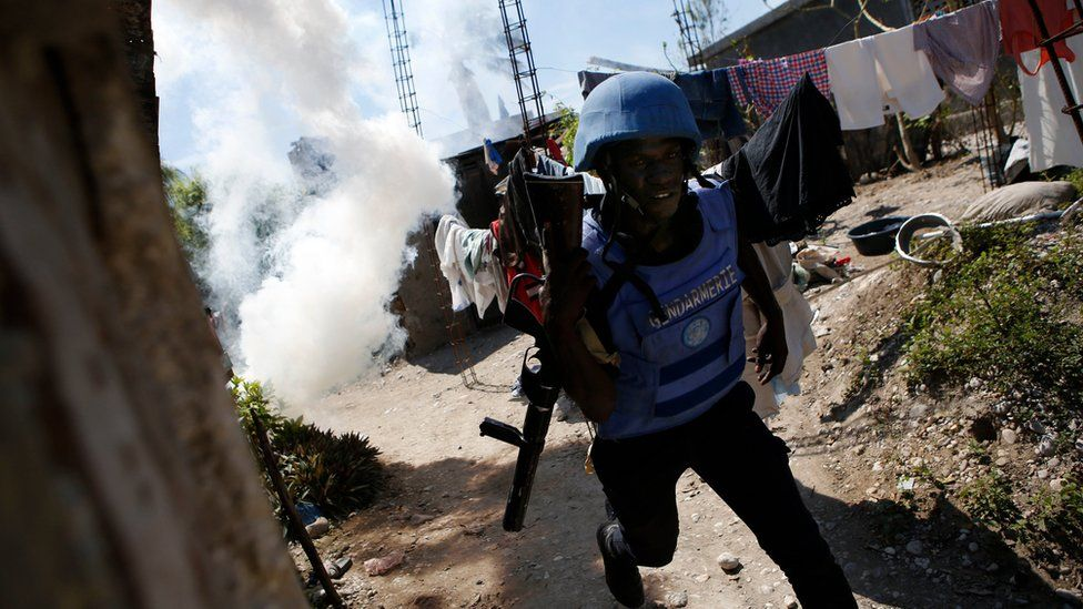 A UN peacekeeper from Senegal runs after throwing a tear gas grenade as security forces clash with rock-throwing residents outside a UN base in Les Cayes