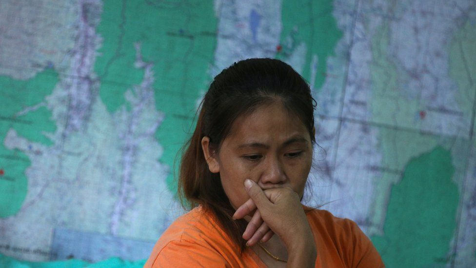 A relative of one of the 12 boys listens to a news conference announcing the diver's death