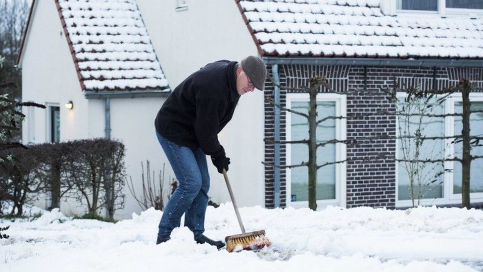 A man clears snow from a path at a house near Nijmegen, in the east of the Netherlands (13 January 2017)