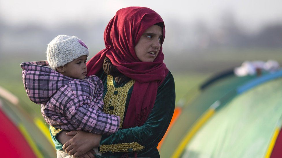 A woman stands outside her tent holding a child in the early morning on the Greek-Macedonia border.