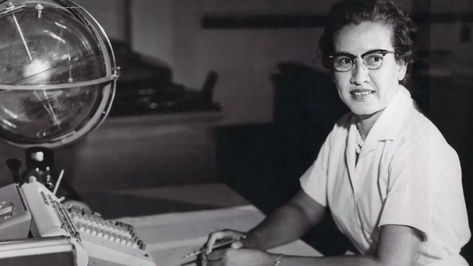Katherine Johnson sits with a globe