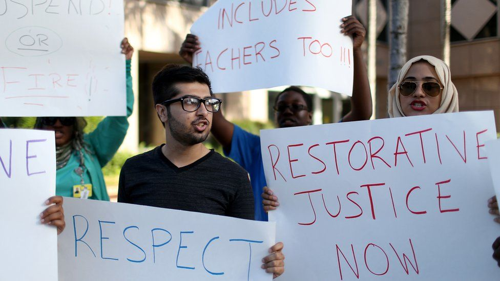 Muhammad Nasim Ul Ghani (L) and Nadine Aly join with other protesters in front of the Broward County School Administrative building demanding action concerning a teacher accused of using an ethnic slur against a Muslim student on March 11, 2015 in Fort Lauderdale, Florida.