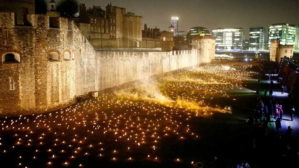 """The moat of the Tower of London are seen filled with thousands of lit torches as part of the installation """"Beyond the Deepening Shadow"""""""