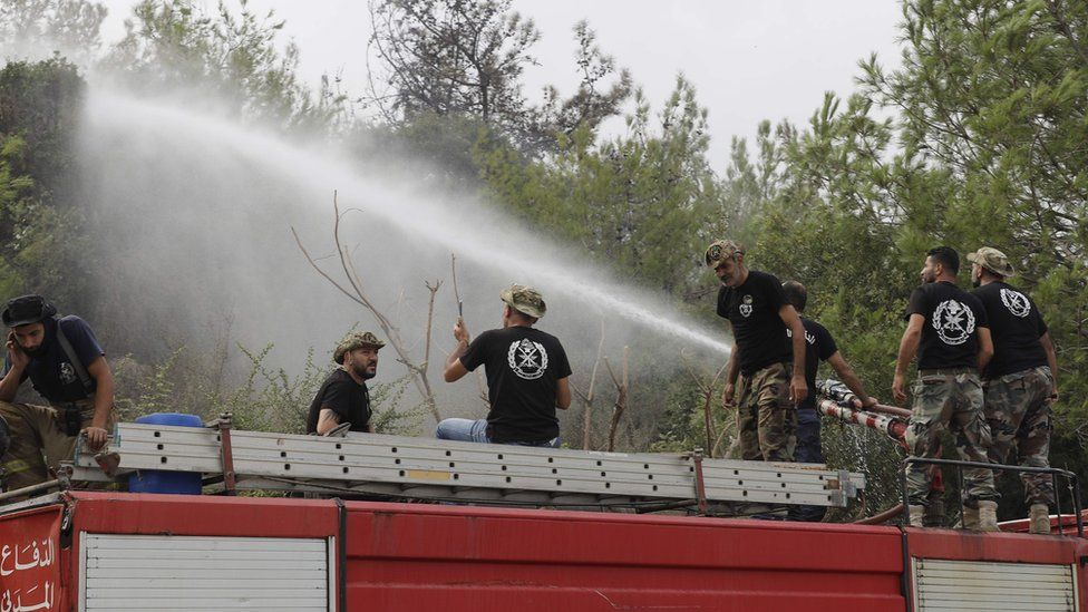 Fire fighters spray water at a fire in Lebanon