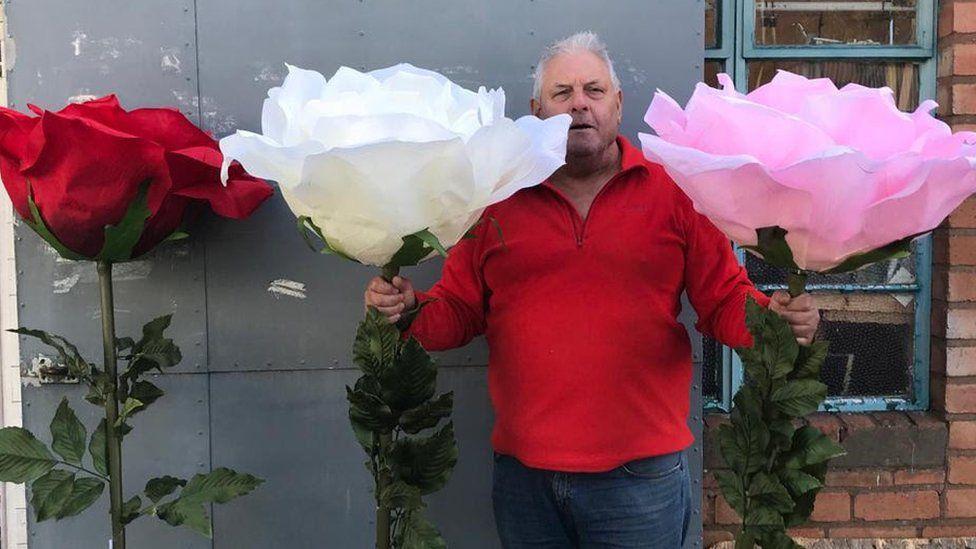 Bill Watson poses alongside large artificial flowers