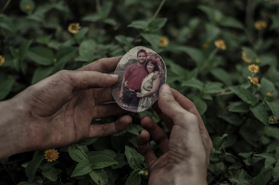 A hand holding a photograph of two people on a locket