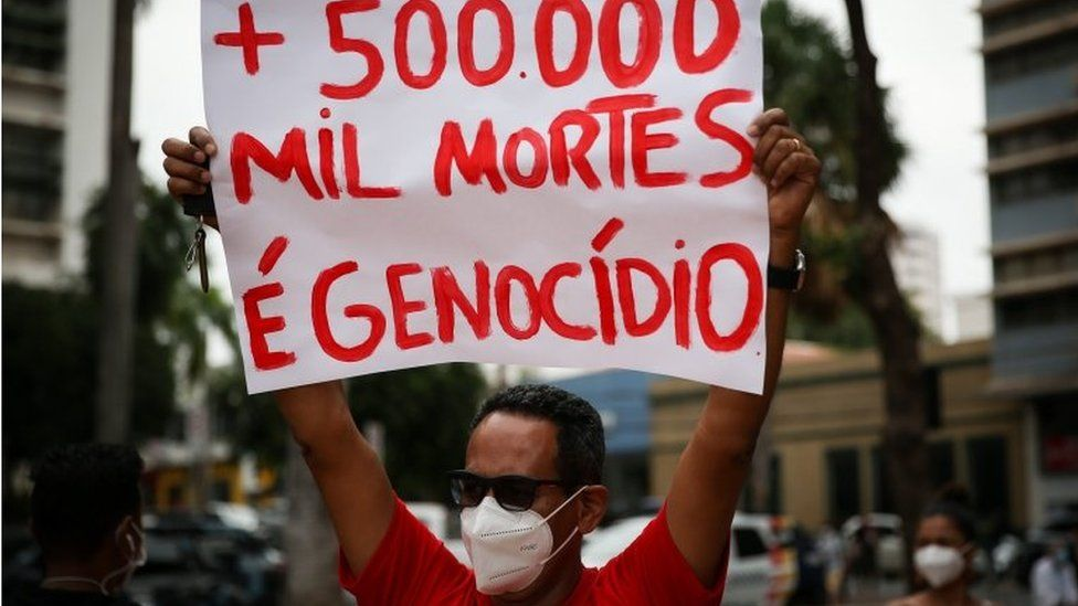 A man at a protest holds a sign calling the deaths genocide
