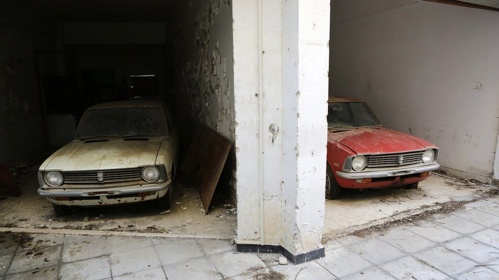In this Wednesday, Jan. 4, 2017 photo cars from the 1970s in an abandoned show room inside the UN buffer zone, Green Line that divided Cyprus