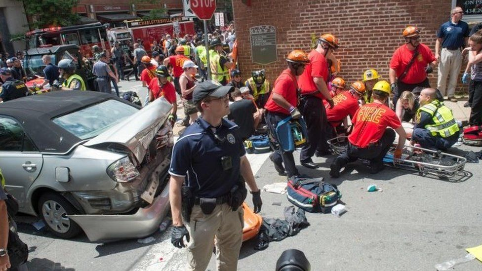 A woman is received first-aid after a car accident ran into a crowd of protesters in Charlottesville, VA on 12 August 2017.