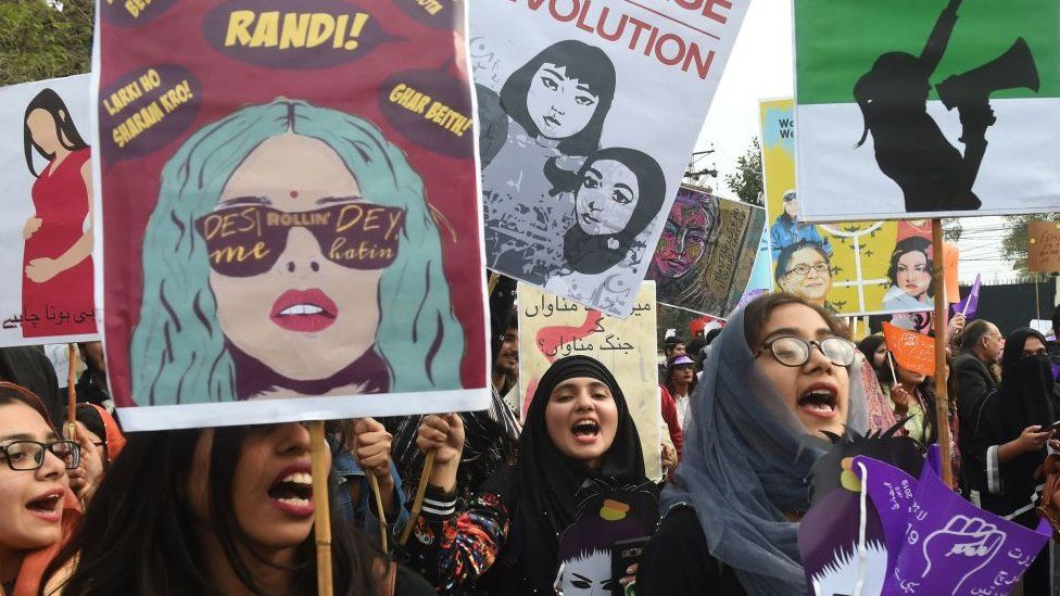 Pakistani civil society activists carry placards and shout slogans during a rally for women rights on International Women's Day in Lahore on March 8, 2019.