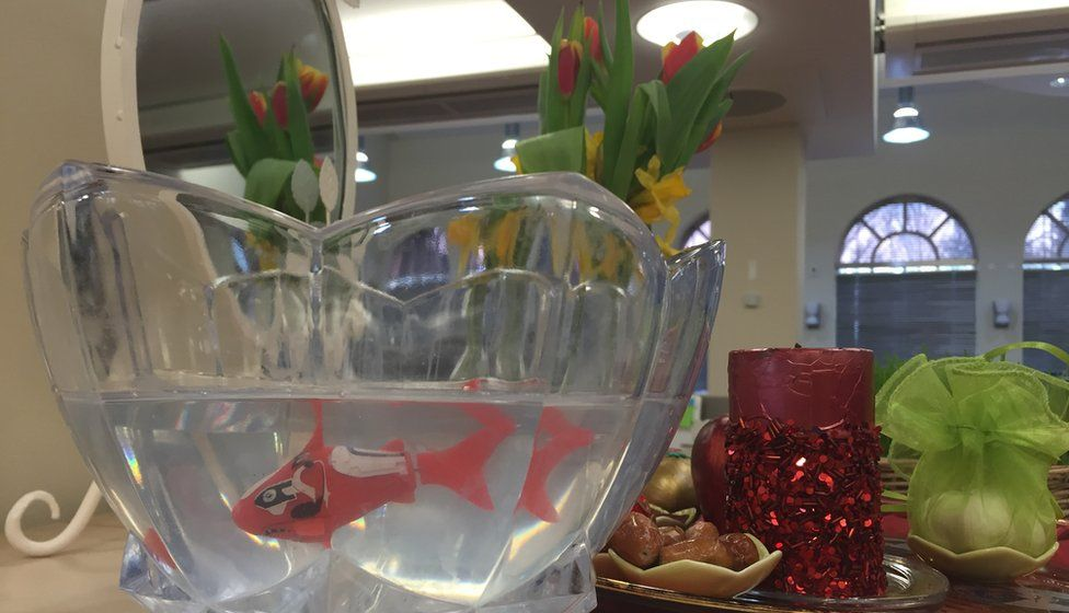 A photo of a Haft Seen table with a plastic goldfish in a bowl