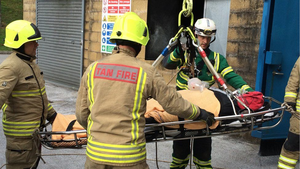 A crane is used to bring a mannequin out of a first storey bedroom in a fire rescue training exercise near Cardiff