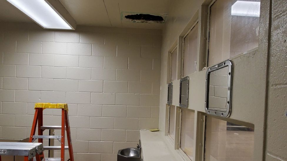 A picture showing a hole in the ceiling of a jail's toilet, where two suspects climbed through